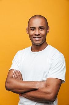 Retrato de un atractivo joven africano casual confiado sonriente de pie sobre la pared amarilla