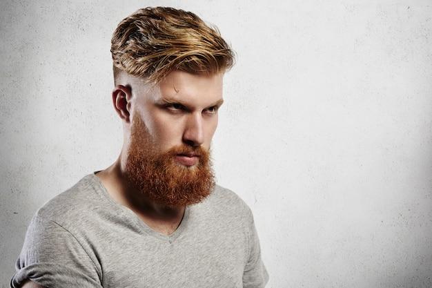 Retrato de atractivo joven caucásico barbudo en casual camiseta gris de pie contra la pared, mirando serio y seguro