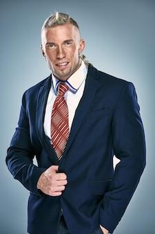 Retrato de un atractivo joven empresario vistiendo traje negro. pelo rubio