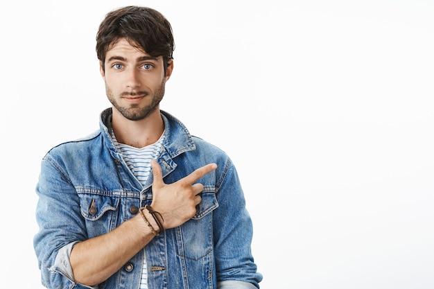 Retrato de atractivo joven hispano con barba y ojos azules apuntando a la esquina superior derecha sonriendo haciendo una pregunta, consultando a un amigo si se enteró de un nuevo café cercano, posando sobre una pared gris