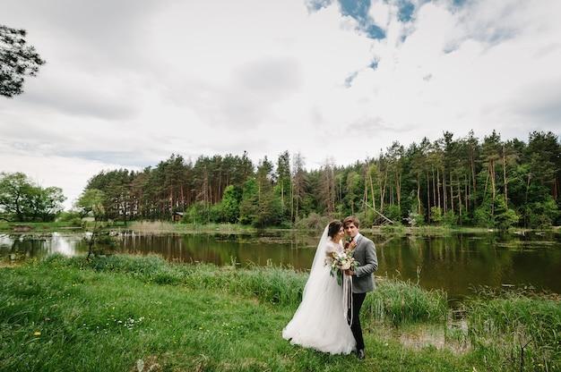 Retrato de un atractivo novio y novia de pie sobre la naturaleza en el parque