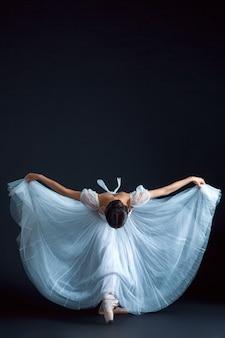 Retrato de la bailarina clásica en vestido blanco sobre pared negra