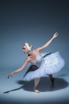 Retrato de la bailarina en el papel de un cisne blanco sobre fondo azul.