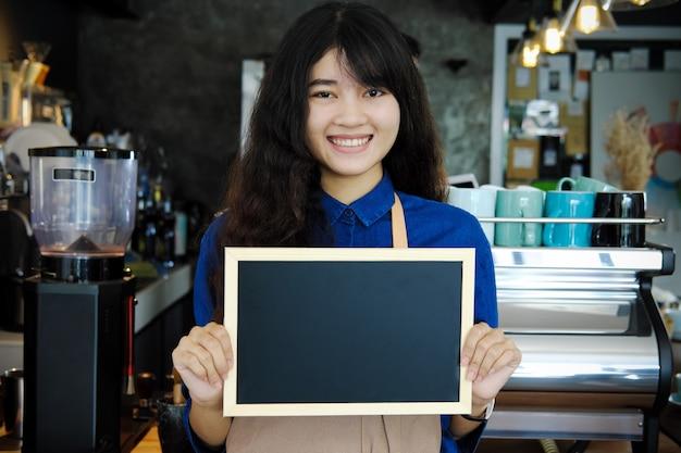 Retrato del barista asiático que sostiene el menú de la pizarra en blanco en cafetería