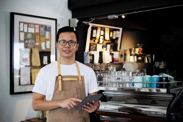 Retrato del barista asiático que sostiene la tableta digital en el contador en cafetería