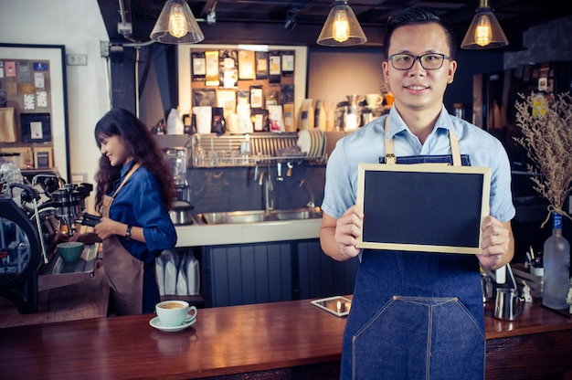 Retrato del barista asiático sonriente que sostiene el menú en blanco de la pizarra en cafetería