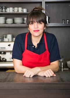 Retrato del barista femenino feliz que se coloca en la cafetería de moda
