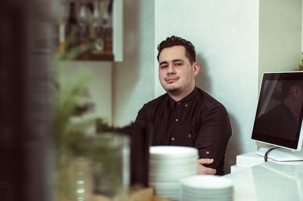 Retrato de un barista de hombre detrás de la barra
