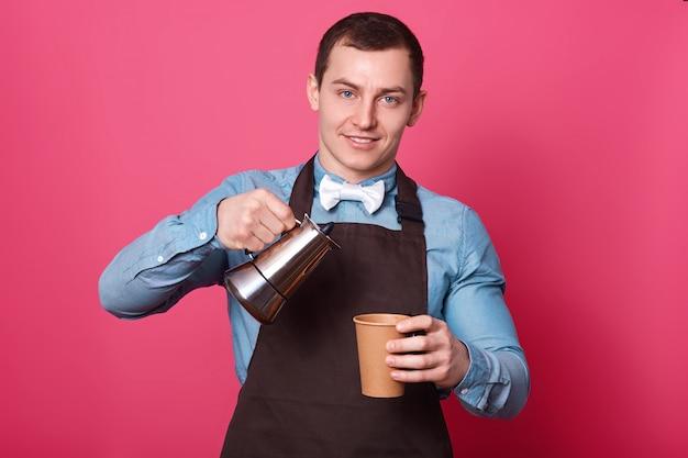 El retrato del barista masculino profesional vierte el café aromático en la taza de papel, viste una camisa azul, una corbata de lazo blanca y un delantal marrón, aislado sobre la pared rosada. joven guapo trabaja en la cafetería.