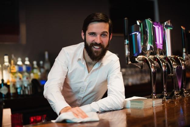 Retrato de barman limpieza barra mostrador