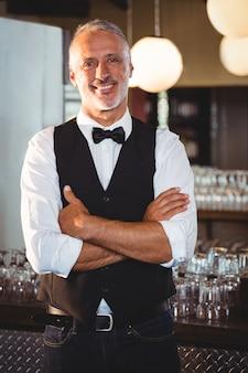 Retrato de barman de pie con los brazos cruzados