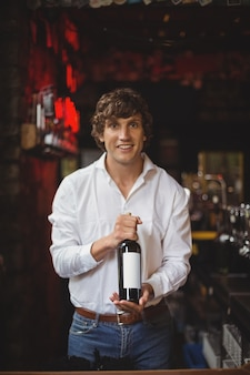 Retrato de barman sosteniendo una botella de vino