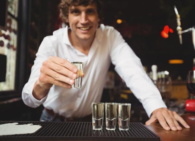 Retrato de barman con vaso de chupito de tequila en barra de bar