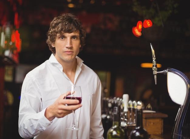 Retrato de barman con vaso de vino tinto