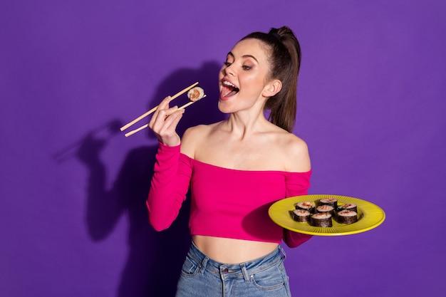 Retrato de bastante alegre niña hambrienta comiendo maki fresco rollo casero aislado sobre fondo de color violeta brillante
