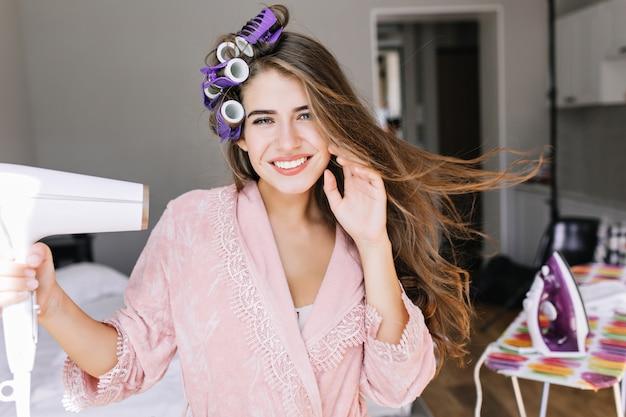 Retrato bastante joven en bata de baño rosa con rizos en la cabeza en casa. ella secando el cabello, sonriendo.