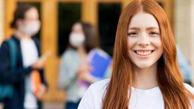 Retrato de bastante joven estudiante sonriendo