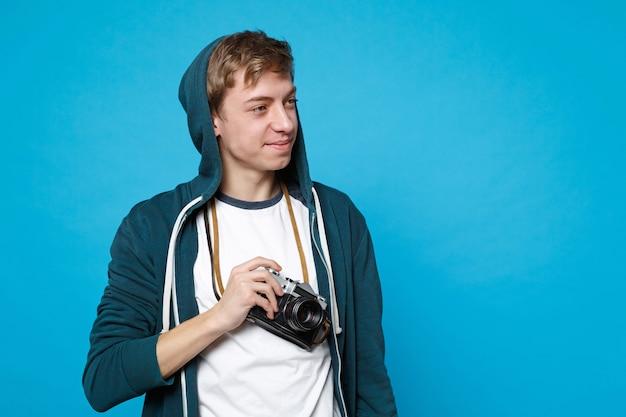 Retrato de bastante joven en ropa casual mirando a un lado, sosteniendo la cámara de fotos vintage retro aislada en la pared azul. personas sinceras emociones, concepto de estilo de vida.