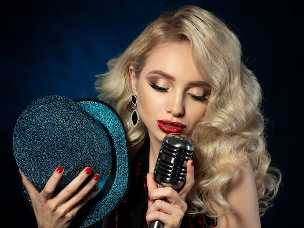 Retrato de bastante rubia cantante sosteniendo micrófono de estilo retro