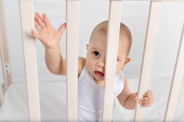 Retrato de un bebé de 8 meses de pie en una cuna en una habitación de niños con ropa blanca y mirando a través de la cama, la mañana del bebé, concepto de productos para bebés