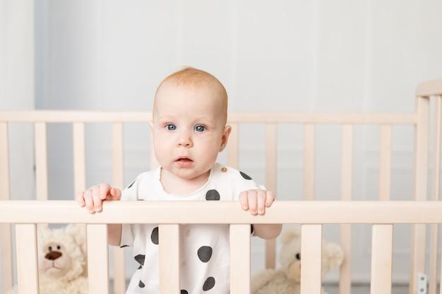 Retrato de un bebé de 8 meses de pie en una cuna con juguetes en pijama en una luminosa habitación infantil después de dormir y mirar a la cámara, un lugar para enviar mensajes de texto
