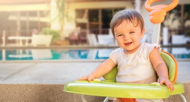 Retrato de un bebé en el andador en el patio trasero