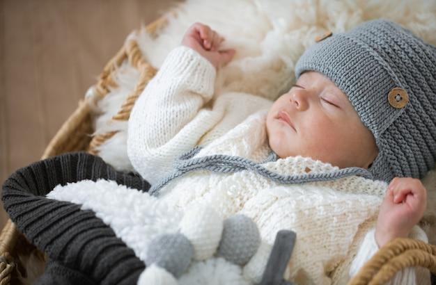 Retrato de un bebé durmiendo en un cálido gorro de punto con un juguete de punto en el mango de cerca.