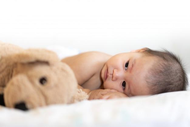 Retrato de bebé feliz descansando en la cama