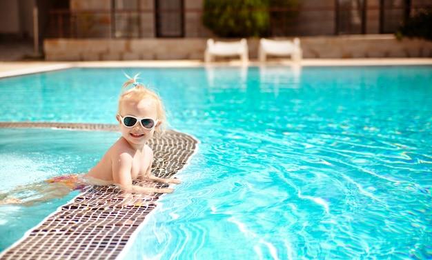 El retrato de un bebé lindo rubio en gafas de sol, nadando en la piscina en las vacaciones de verano.