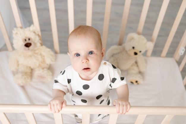 Retrato de un bebé de pie en una cuna con juguetes en pijama después de dormir