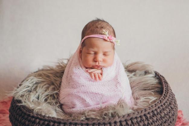Retrato de un bebé recién nacido durmiendo en una diadema con flores. concepto de salud: fiv, accesorios para bebés.
