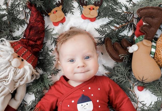 Retrato de un bebé rubio con juguetes navideños