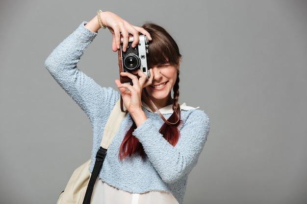 Retrato de una bella colegiala sonriente tomando foto