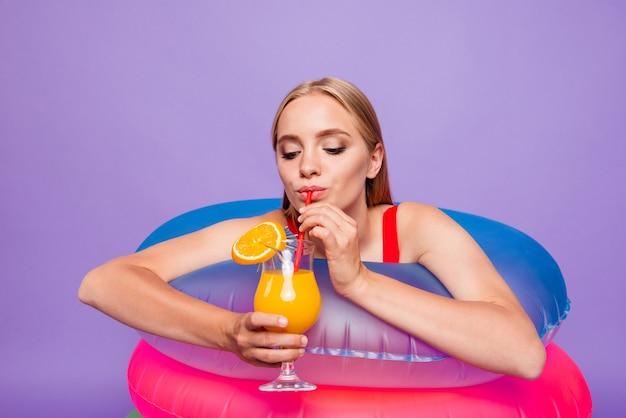 Retrato de bella dama disfrutando de beber en la piscina