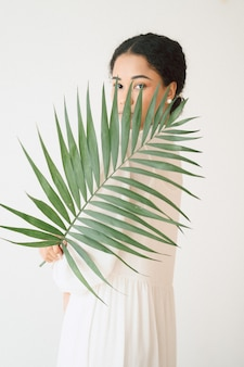 Retrato de bella dama en la habitación vacía de pie mirando y sosteniendo la rama de palma en vestido blanco largo