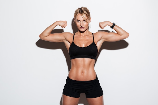 Retrato de una bella deportista muscular flexionando sus músculos