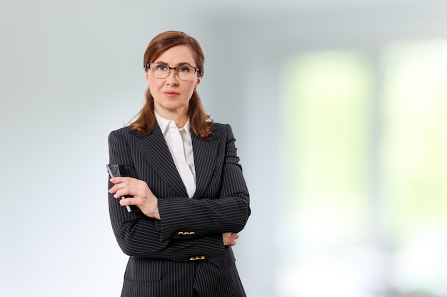 Retrato de una bella empresaria de 50 oídos con teléfono móvil en la oficina.