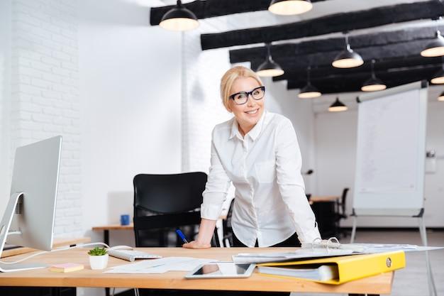 Retrato de una bella empresaria madura sonriente de pie cerca de su lugar de trabajo