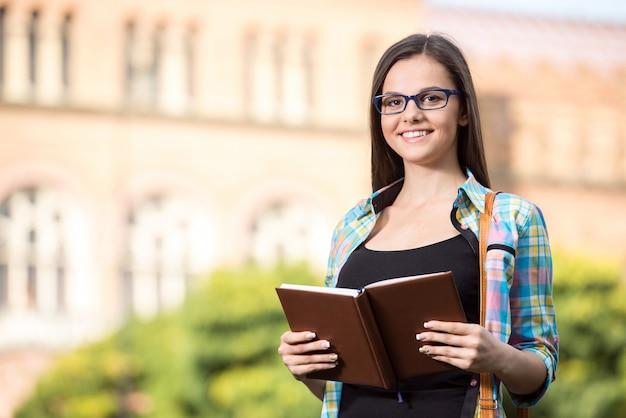 Retrato de una bella estudiante con edificio universitario.
