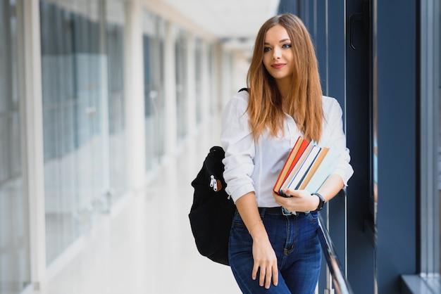 Retrato de una bella estudiante con libros y una mochila en el pasillo de la universidad.
