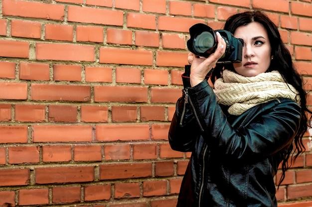 Retrato de una bella fotógrafa morena con el pelo largo y rizado en ropa cálida de otoño