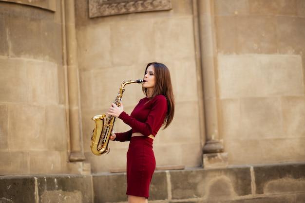 Retrato de una bella joven caminando por la calle con un saxofón
