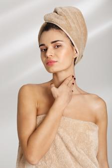 Retrato de una bella joven elegante después del baño de pie cubierto de toalla.