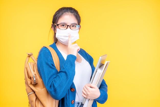 Retrato de una bella joven estudiante con una máscara sosteniendo un libro de texto - estudiando el sistema de e-learning en línea
