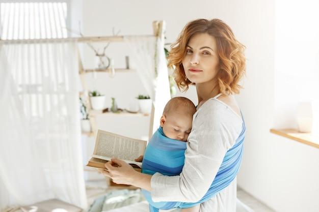 Retrato de una bella joven madre con hijo dormido en el pecho y el libro en las manos. la mujer gira la cabeza para mirar al esposo con amor y felicidad.