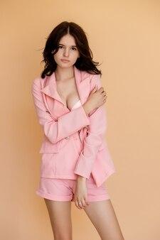 Retrato de una bella joven morena vestida con traje de verano rosa