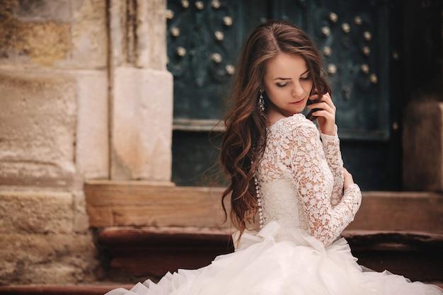 Retrato de una bella joven novia, cerca del edificio antiguo