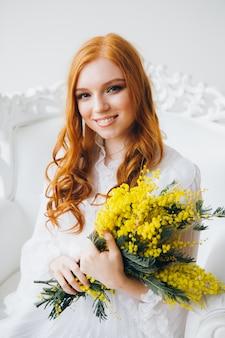 Retrato de una bella joven pelirroja con una mimosa en un vestido blanco largo