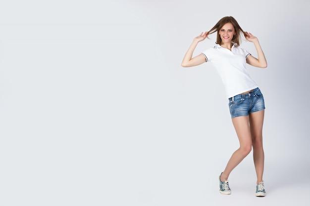 Retrato de bella joven sonriente de pie chica en una camiseta blanca, pantalones cortos azules y zapatillas de deporte aisladas