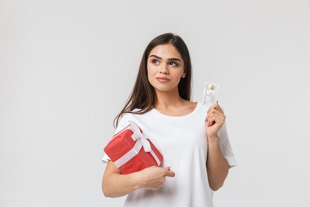 Retrato de una bella joven vestida casualy de pie aislado en blanco, sosteniendo la caja de regalo, mostrando la tarjeta de crédito